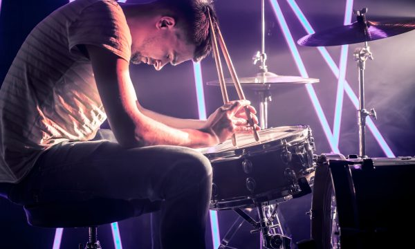 pensive man playing the drums, playing the drums with sticks close-up. Against the background of colored lights and a bright beam of light. Musical concept with a working drum.