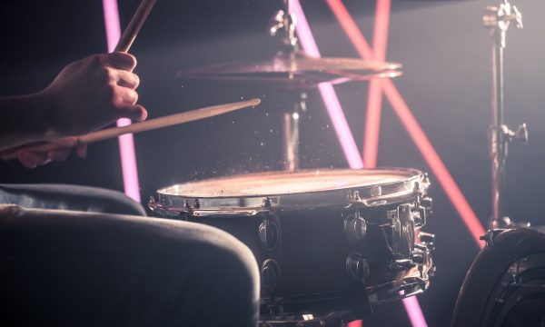 the man plays the drums, the game is on the working drum with sticks close-up. On the background of colored lights. Musical concept with a working drum.