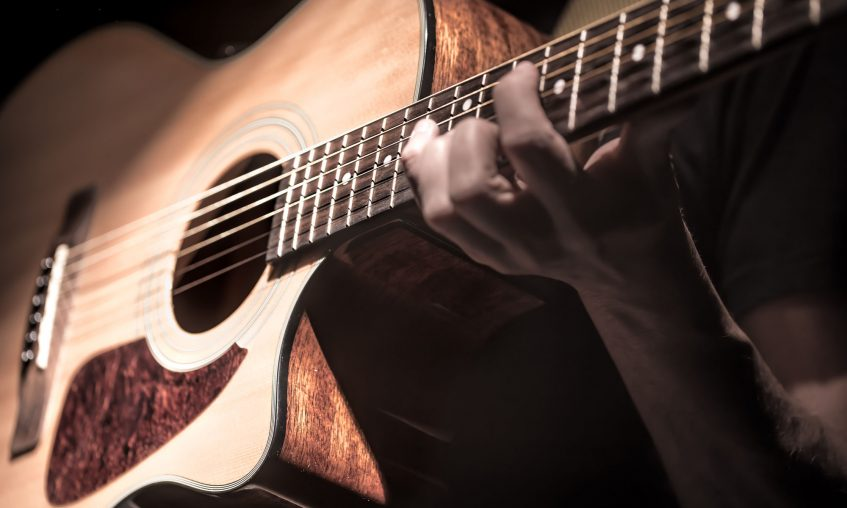 Man playing acoustic guitar on dark background, guitar closeup. A musical concept.