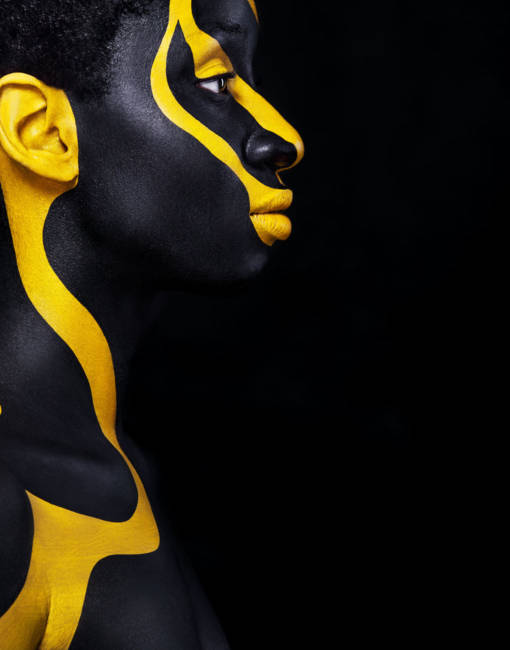 Art fashion makeup. An amazing woman with black makeup and leaking gold paint